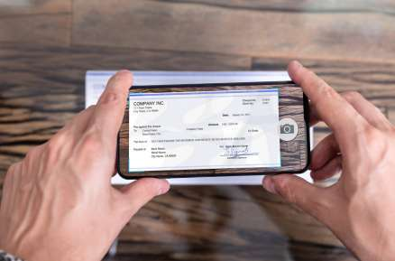 man's hands taking scan of a check using a smart phone app